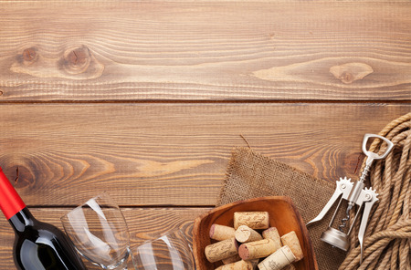 Red wine bottle, glasses, bowl with corks and corkscrew. View from above over rustic wooden table background with copy space