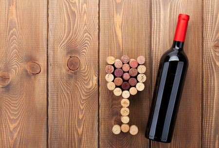 Red wine bottle and glass shaped corks. Over rustic wooden table background with copy space Stock Photo