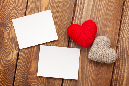 Photo frames and handmaded valentines day toy hearts over white wooden background photo