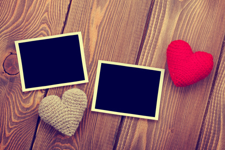 Photo frames and handmaded valentines day toy hearts over wooden background. Toned image