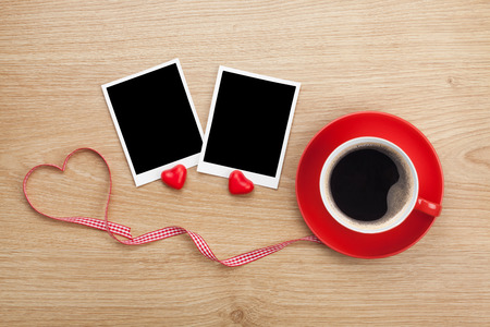 Blank photo frames and red coffee cup on wooden background photo