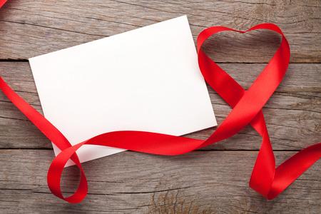 Fotorámeček nebo dárkové karty s valentýnský tvaru srdce pásem karet přes dřevěný stůl pozadí