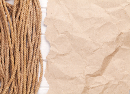 rumpled: Brown rumpled cardboard paper background with marine rope and copy space Stock Photo