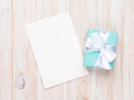 cajas navide�as: Caja de regalo de d�a de San Valent�n y tarjeta de felicitaci�n en mesa de madera blanca con espacio de copia