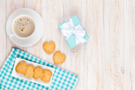 coffee cake: Cup of coffee, heart shaped cookies and gift box on white wooden table with copy space