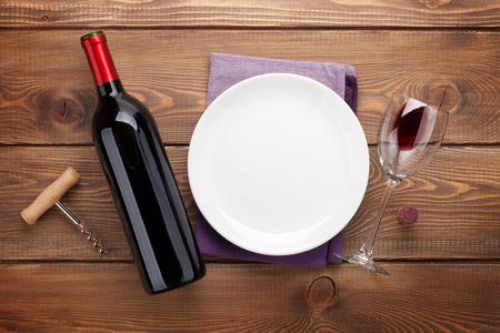 copa de vino: Mesa con plato vac�o, copa de vino y una botella de vino tinto.