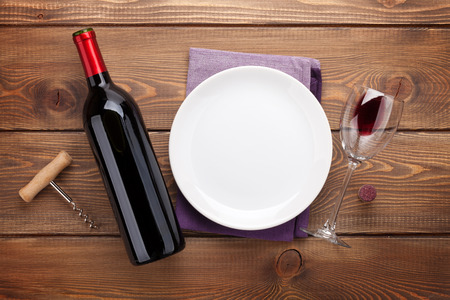 wine glass: Table setting with empty plate, wine glass and red wine bottle.