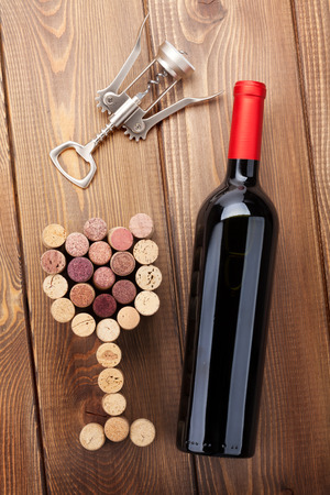 Red wine bottle, glass shaped corks and corkscrew.