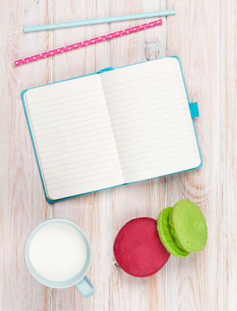 Cup of milk and macarons on white wooden table with notepad for copy space photo