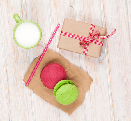 Colorful macarons, cup of milk and gift box on white wooden table photo