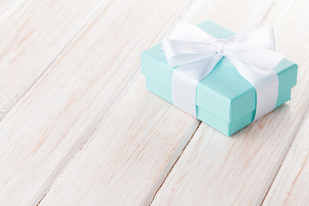 Gift box with bow over white wooden table with copy space Archivio Fotografico