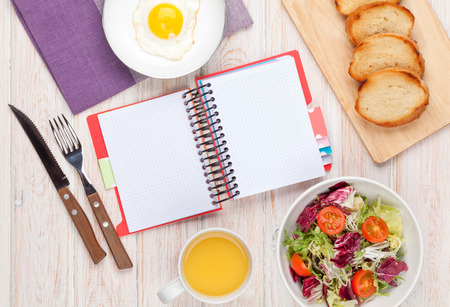 todo: Healthy breakfast with fried egg, toasts and salad on white wooden table with notepad for copy space