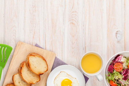 english breakfast: Healthy breakfast with fried egg, toasts and salad on white wooden table with copy space Stock Photo