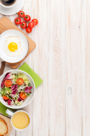 Healthy breakfast with fried egg, toasts and salad on white wooden table with copy space Фото со стока