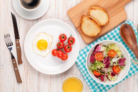 desayuno: Desayuno saludable con huevo frito, tostadas y ensalada en la mesa de madera blanca