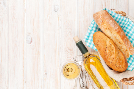 basket: White wine and bread on white wooden table background with copy space