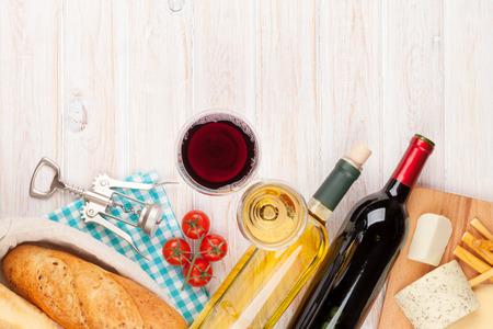 pan y vino: Blanco y rojo copas de vino, el queso y el pan en el fondo blanco mesa de madera con espacio de copia