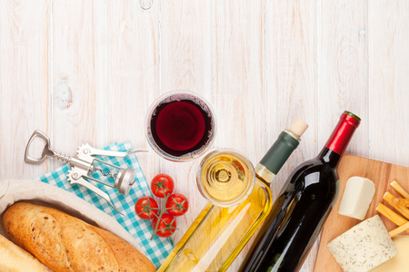 White and red wine glasses, cheese and bread on white wooden table background with copy space Stock Photo