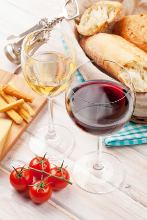 White and red wine glasses, cheese and bread on white wooden table background photo