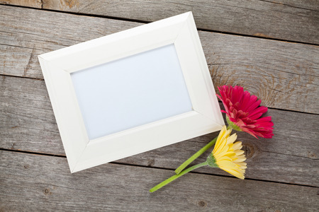 nature photo: Two colorful gerbera flowers and photo frame on wooden table