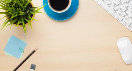 커피 컵, 컴퓨터와 꽃과 함께 사무실 테이블. 복사 공간 위에서 볼
