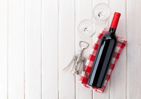 Red wine bottle, glasses and corkscrew on white wooden table background with copy space Banco de Imagens