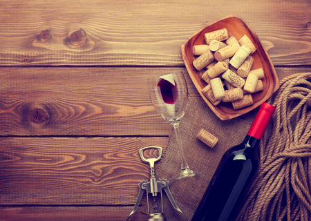 Red wine bottle, glass and corkscrew on wooden table background with copy space. Retro toned photo