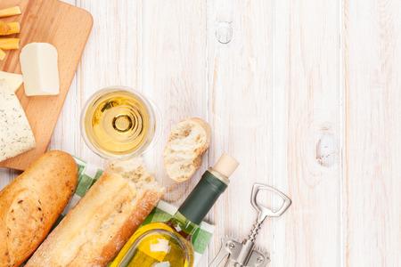 Witte wijn, kaas en brood op witte houten tafel achtergrond met een kopie ruimte