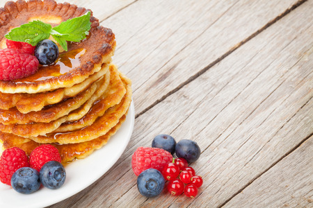 Pancakes with raspberry, blueberry, mint and honey syrup. On wooden table with copy space photo