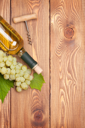 glass table: White wine bottle and bunch of white grapes on wooden table background with copy space