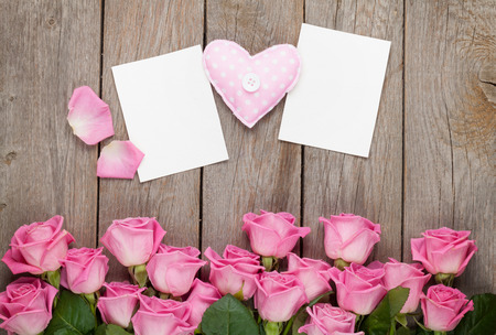 wedding table decor: Pink roses, handmaded toy heart and valentines day blank greeting cards or photo frames over wooden table. Top view with copy space