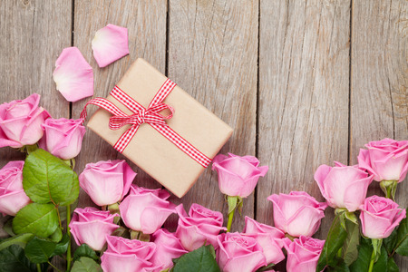 flower boxes: Valentines day background with pink roses over wooden table and gift box. Top view with copy space