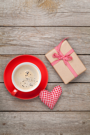 Valentines day gift box, toy heart and coffee cup over wooden table with copy space photo