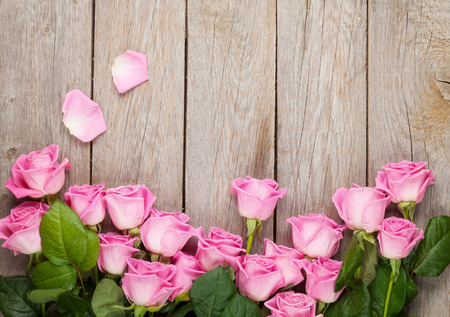 mother board: Valentines day background with pink roses over wooden table. Top view with copy space