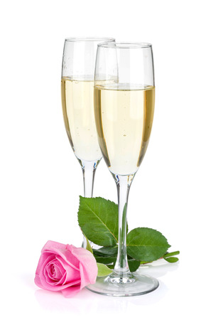 Two champagne glasses and pink rose flower. Isolated on white background photo