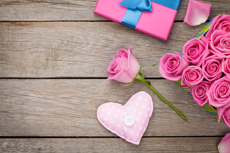 beautiful flowers: Valentines day background with gift box full of pink roses and handmaded toy heart over wooden table. Top view with copy space