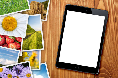 season photos: Tablet with blank screen and stack of printed pictures collage on wooden table