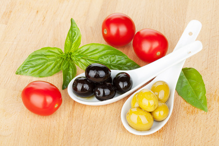 Olives, tomatoes and basil on wood table photo