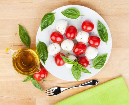 salad plate: Piatto di insalata caprese su tavola di legno