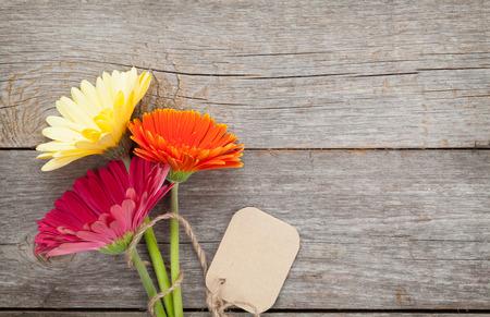 flores de cumplea�os: Tres flores de gerbera coloridos con etiqueta en la mesa de madera Foto de archivo