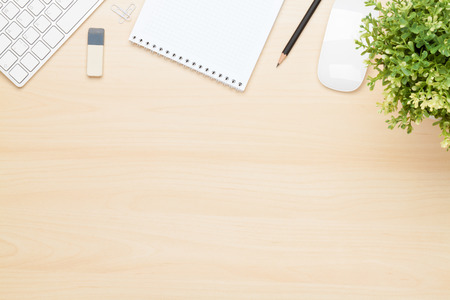 tabulka: Kancelářský stůl s poznámkový blok, počítač a květin. Pohled shora s kopií vesmíru Reklamní fotografie