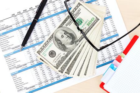 cuadro sinoptico: Escritorio de oficina con los informes, la libreta en blanco y dinero en efectivo. Vista desde arriba Foto de archivo