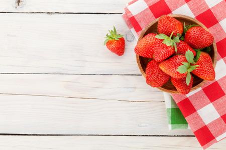 Verse rijpe aardbeien in kom op houten tafel achtergrond. Bovenaanzicht met een kopie ruimte Stockfoto