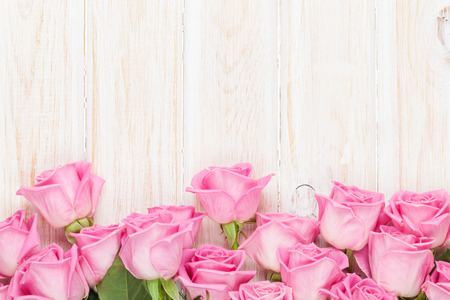 Valentines day background with pink roses over wooden table. Top view with copy space