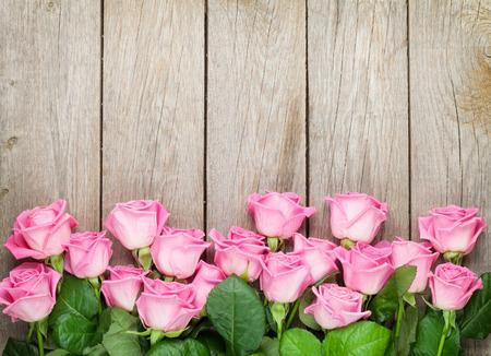 木製のテーブルの上のピンクのバラとバレンタインデーの背景。コピー スペース平面図