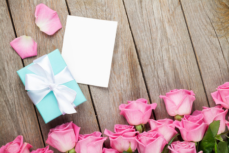 floral bouquet: Pink roses and valentines day greeting card or photo frame and gift box over wooden table. Top view with copy space