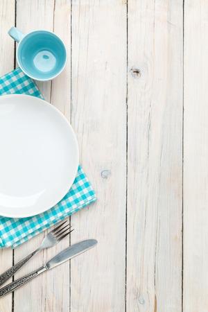Lege plaat, zilverwerk en handdoek over houten tafel achtergrond. Zicht van bovenaf met een kopie ruimte
