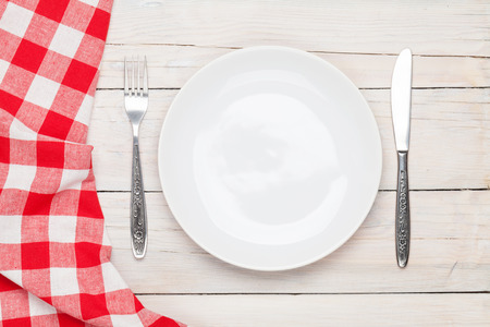 Empty plate, silverware and towel over wooden table background. View from above with copy space photo