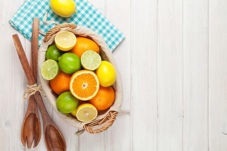 frutas tropicales: Las frutas c�tricas en la cesta. Las naranjas, limas y limones. Sobre fondo mesa de madera con espacio de copia