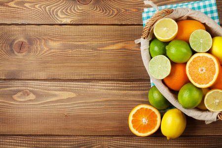 Citrus fruits in basket. Oranges, limes and lemons. Top view over wooden table background with copy space Imagens